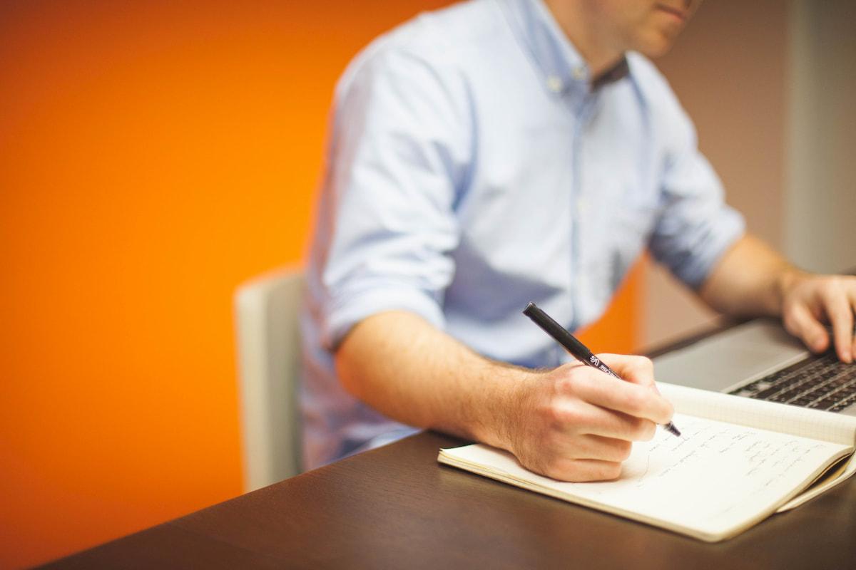 Man werkt en schrijft op een stuk papier